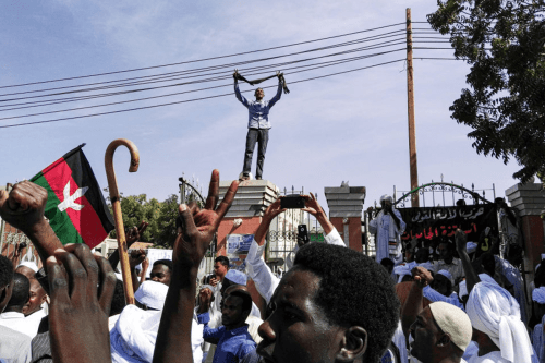 A Sudanese protester flashes the victory gesture as he stands atop a gatehouse while others chant slogans and wave the flag of the opposition Umma Party led by Sadiq al-Mahdi, during a demonstration in the capital Khartoum's twin city of Omdurman on 25 January 2019 [AFP/Getty Images]