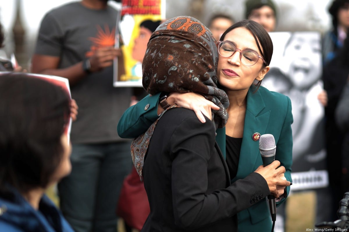 U.S. Rep. Alexandria Ocasio-Cortez (D-NY) (R) hugs Rep. Ilhan Omar (D-MN) (L) during a news conference at the East Front of the U.S. Capitol 7 February 2019 in Washington, DC. [Alex Wong/Getty Images]