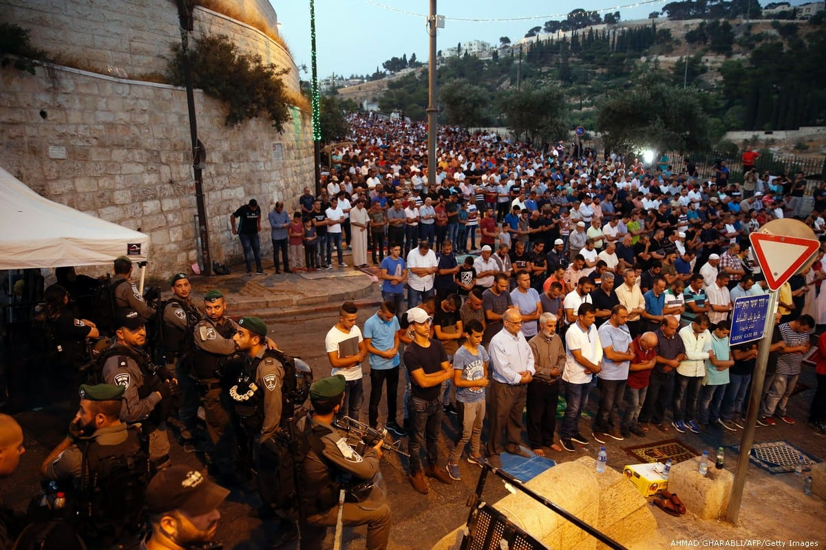 Israeli security forces stand by as Palestinian Muslim worshippers pray outside Lions' Gate in Jerusalem on 24 July 2017 [AHMAD GHARABLI/AFP/Getty Images]
