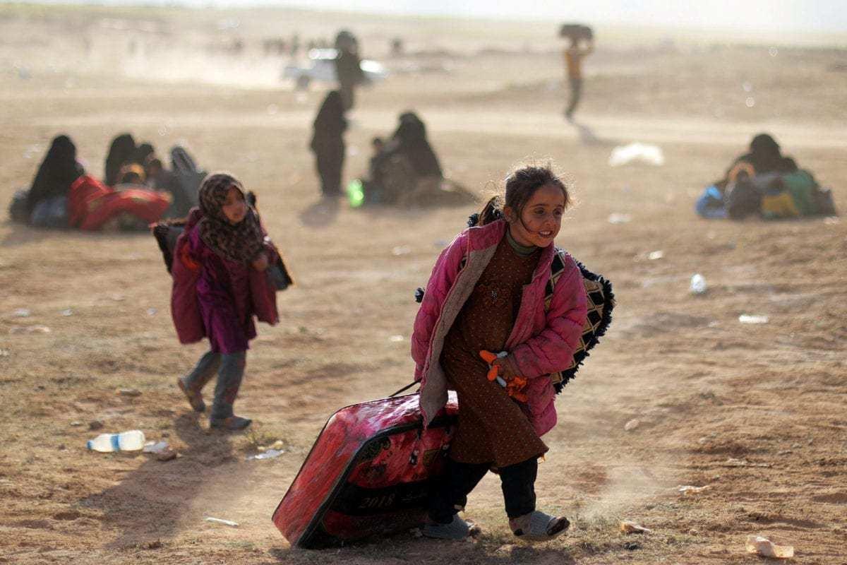 A girl walks with her belongings near Baghouz, Deir Al Zor province, Syria March 5, 2019 [REUTERS/ Rodi Said]