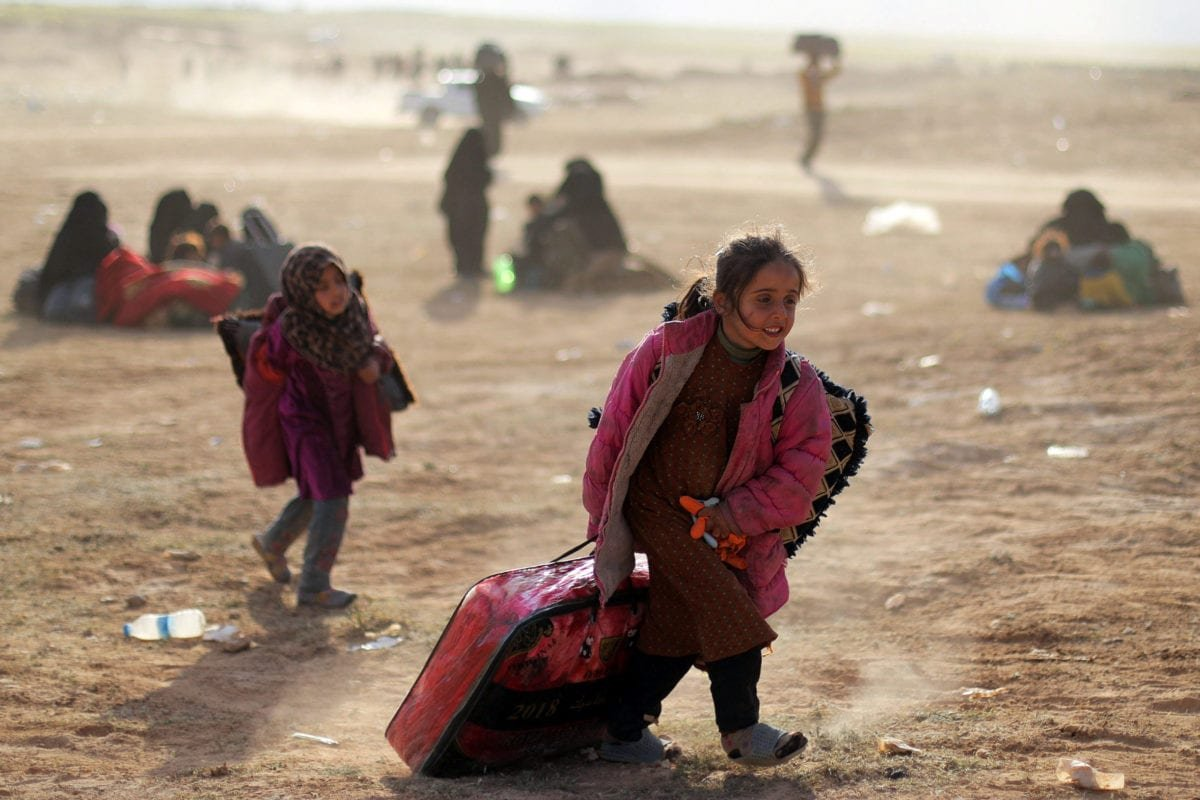 A girl walks with her belongings near Baghouz, Deir Al Zor province, Syria March 5, 2019 [REUTERS/ Rodi Said]