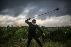 """A Palestinian man throws rock in response to Israeli forces' intervention during """"Great March of Return"""" demonstration near Israel-Gaza border, in Khan Yunis, Gaza on March 01, 2019. ( Mustafa Hassona - Anadolu Agency )"""