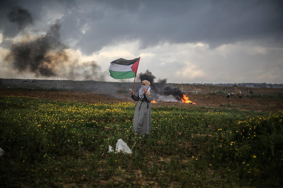 "A Palestinian woman waves a Palestinian flag during ""Great March of Return"" demonstration near Israel-Gaza border, in Khan Yunis, Gaza on March 01, 2019 [Mustafa Hassona / Anadolu Agency]"