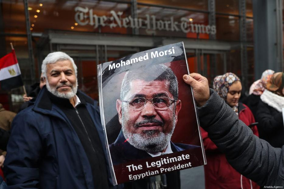 A man holds a poster of the late former Egyptian president Mohammed Morsi during a protest in New York, US on 2 March 2019 [Atılgan Özdil/Anadolu Agency]