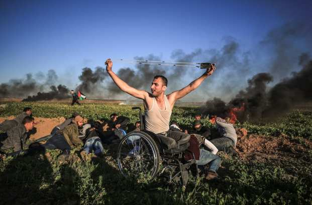 "A Palestinian disabled man throws a stone with a slingshot towards Israeli security forces during the ""Great March of Return"" demonstration near the Shuja'iyya neighborhood in Gaza City, Gaza on 8 March, 2019 [Ali Jadallah/Anadolu Agency]"