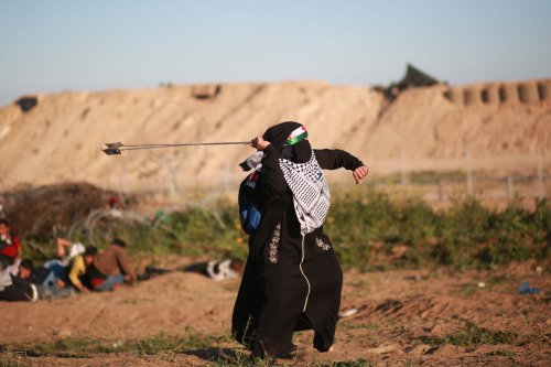 "A Palestinian woman uses slingshot to throw stone to Israeli forces during a""Great March of Return"" demonstration near Al Bureij Refugee Camp in Gaza City, Gaza on 8 March, 2019 [Hassan Jedi/Anadolu Agency]"