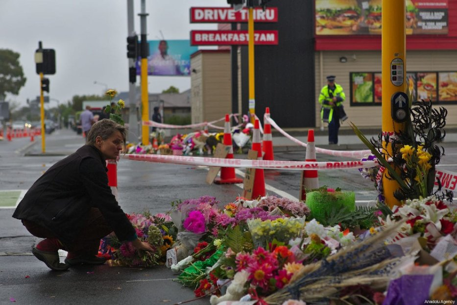 A woman lays flowers to pay tribute at Linwood Ave public vigil, close to the Linwood Mosque shooting area, for victims who lost their lives during twin terror attacks in New Zealand mosques in Christchurch, New Zealand on March 17, 2019. [Peter Adones - Anadolu Agency]