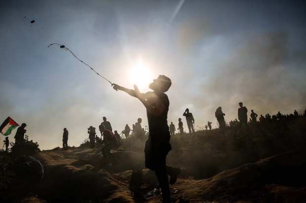 """A Palestinian throws rock in response to Israeli forces' intervention during a protest within """"Great March of Return"""" demonstrations near Al Bureij Refugee Camp in Gaza City, Gaza on March 22, 2019. ( Hassan Jedi - Anadolu Agency )"""