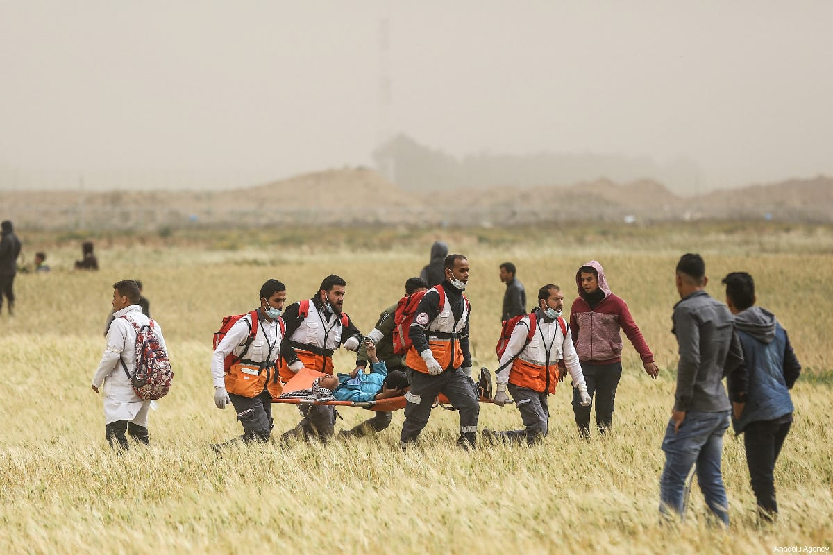 "Palestinian medical staff carry away an injured Palestinian during a protest within the ""Great March of Return"" and ""Palestinian Land Day"" demonstrations at Israel-Gaza border in Khan Yunis, Gaza on 30 March 2019. [Mustafa Hassona - Anadolu Agency]"