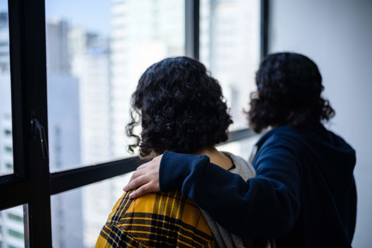 Saudi sisters Rawan (in yellow), 18, and Reem, 20, (both using adopted aliases) stand next to each other during an interview with AFP in Hong Kong on February 22, 2019. [ANTHONY WALLACE/AFP/Getty Images]