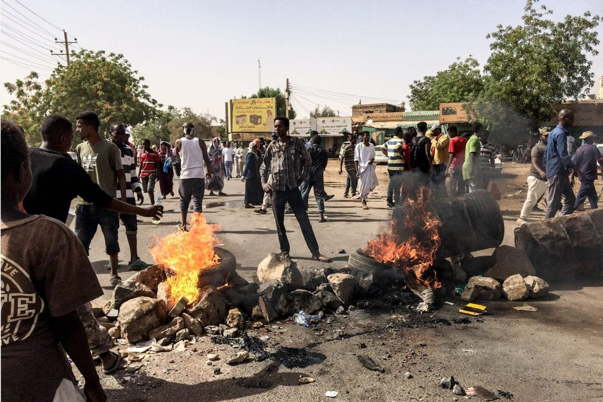Sudanese protesters set up a burning barricade during demonstrations outside the military headquarters in Khartoum, Sudan on 11 April 2019. [Stringer - Anadolu Agency]