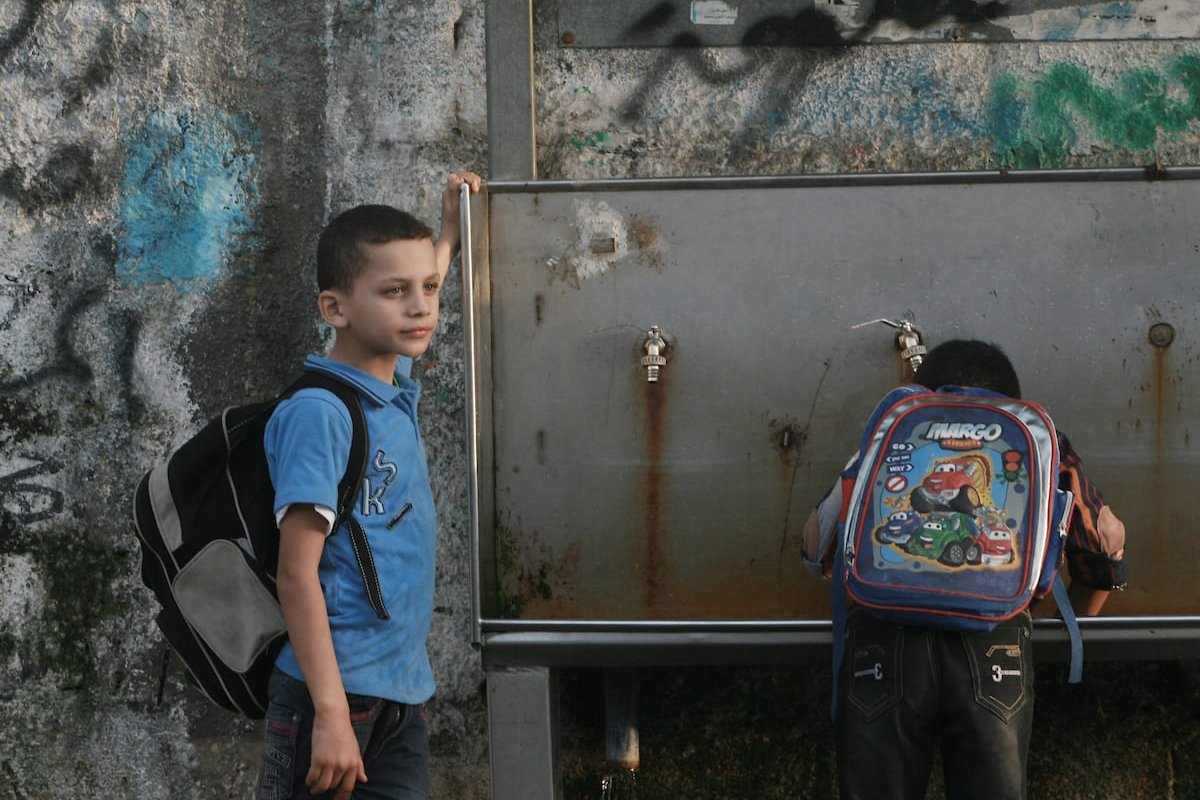 Palestinian boys drink water from a public tap in Rafah refugee camp in southern Gaza Strip, Oct. 30, 2013. [Eyad Al Baba/Middle East Monitor]