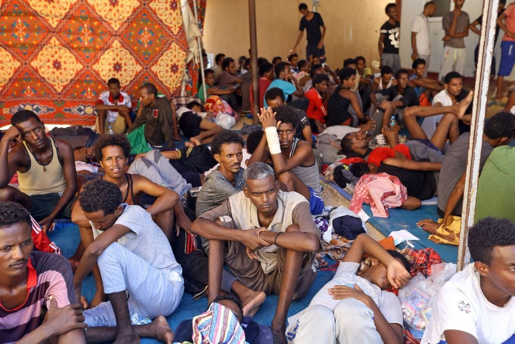 Illegal migrants sit inside the Ganzour shelter after being transferred from in the airport road due to fighting in the Libyan capital Tripoli on 5 September, 2018 [MAHMUD TURKIA/AFP/Getty Images]