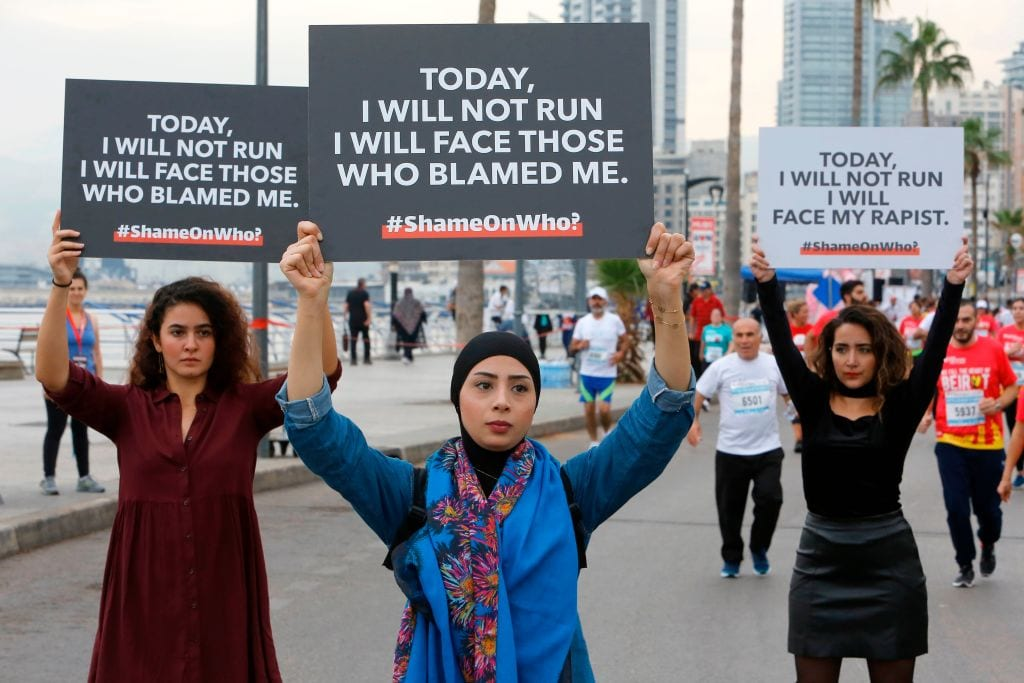 Protesters hold banners with messages against sexual assault during the 16th edition of the Beirut Marathon in the Lebanese capital on 11 November, 2018 [MARWAN TAHTAH/AFP/Getty Images]