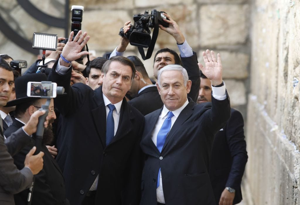 Brazilian President Jair Bolsonaro (L) and Israeli Prime Minister Benjamin Netanyahu wave to the press during a visit to the Western wall, the holiest site where Jews can pray, in the Old City of Jerusalem on 1 April, 2019 [MENAHEM KAHANA/AFP/Getty Images]