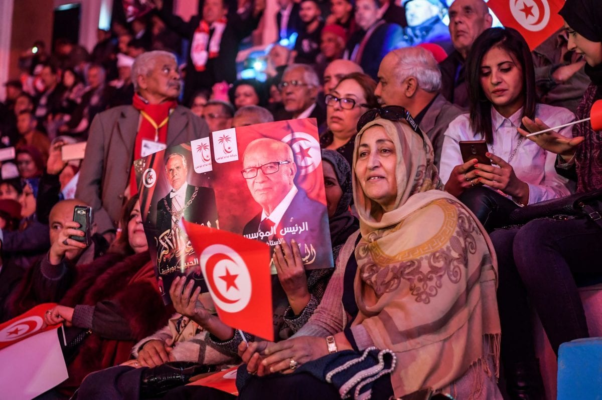 """Supporters of Tunisian President Beji Caid Essebsi wave posters depicting his portrait (L) alongside that of the country's founding father Habib Bourguiba, with a caption below the former reading reading in Arabic """"the founding president"""" and the latter """"the greater warrior"""", during the Nidaa Tounes Party congress in the coastal city of Monastir, about 160 kilometres south of the capital Tunis, on 6 April 2019. [FETHI BELAID / AFP / Getty]"""
