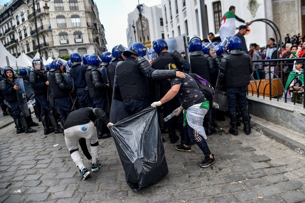 Algerian youths collect trash behind riot police during an anti-regime demonstration in Algiers, Algeria on 10 April 2019 [RYAD KRAMDI/AFP/Getty]