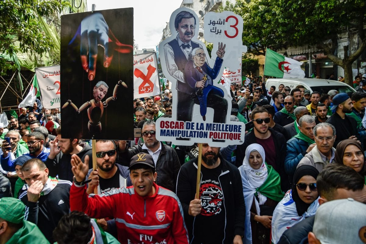 Algerians chant slogans and march with protest signs as they gather for an anti-government demonstration in the capital Algiers on April 12, 2019. [RYAD KRAMDI / AFP / Getty]