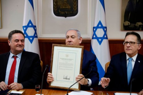 Israeli Prime Minister Benjamin Netanyahu (C) holds a proclamation signed by US President Donald Trump recognizing Israel's sovereignty over the Golan Heights, during a weekly cabinet meeting in Jerusalem on 14 April, 2019 [RONEN ZVULUN/AFP/Getty Images]
