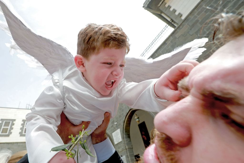 A toddler in angel costume pinches a man as Catholic believers gather outside Greek-Melkite Patriarchal Cathedral of the Dormition of Our Lady to mark Palm Sunday in the capital Damascus in Bab Sharki, Old Damascus on 14 April, 2019 [LOUAI BESHARA/AFP/Getty Images]
