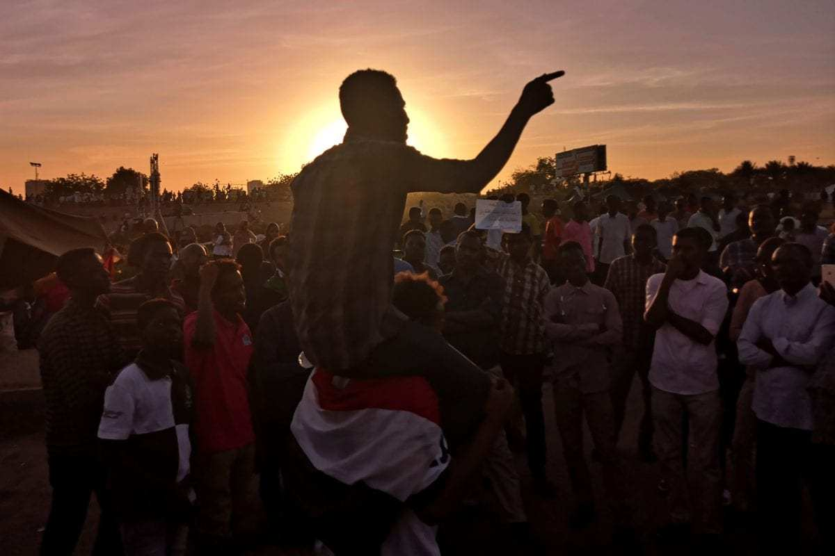 Sudanese protesters rally in the area of the military headquarters in the capital Khartoum at sunset on 15 April 2019. [Ashraf SHAZLY / AFP / Getty]