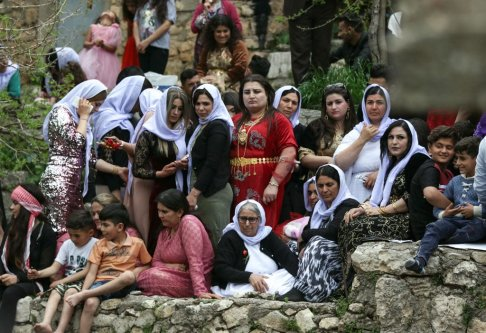Iraqi Yazidi women gather outside the Temple of Lalish, in a valley near the Kurdish city of Dohuk on 16 April, 2019 [SAFIN HAMED/AFP/Getty Images]