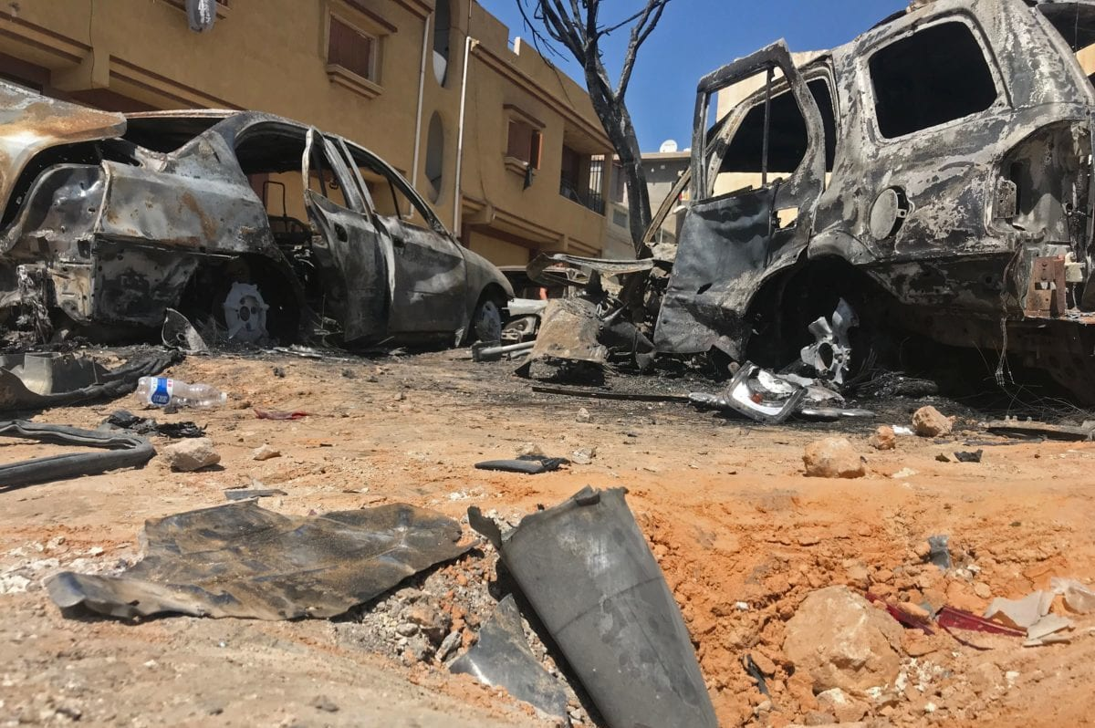 A picture taken on April 17, 2019 shows remnants of a rocket and burnt vehicles at the scene of an overnight rocket attack which no group claimed responsibility for so far in the Libyan capital Tripoli. [Mahmud TURKIA / AFP / Getty]