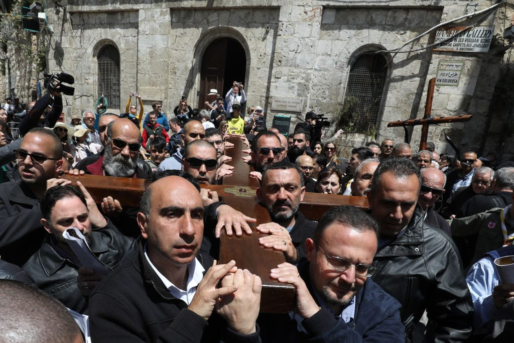 Members of the local Catholic Palestinian parish carry a wooden cross along the Via Dolorosa (Way of Suffering) in Jerusalem's Old City during the Good Friday procession on 19 April 2019. [GALI TIBBON/AFP/Getty Images]