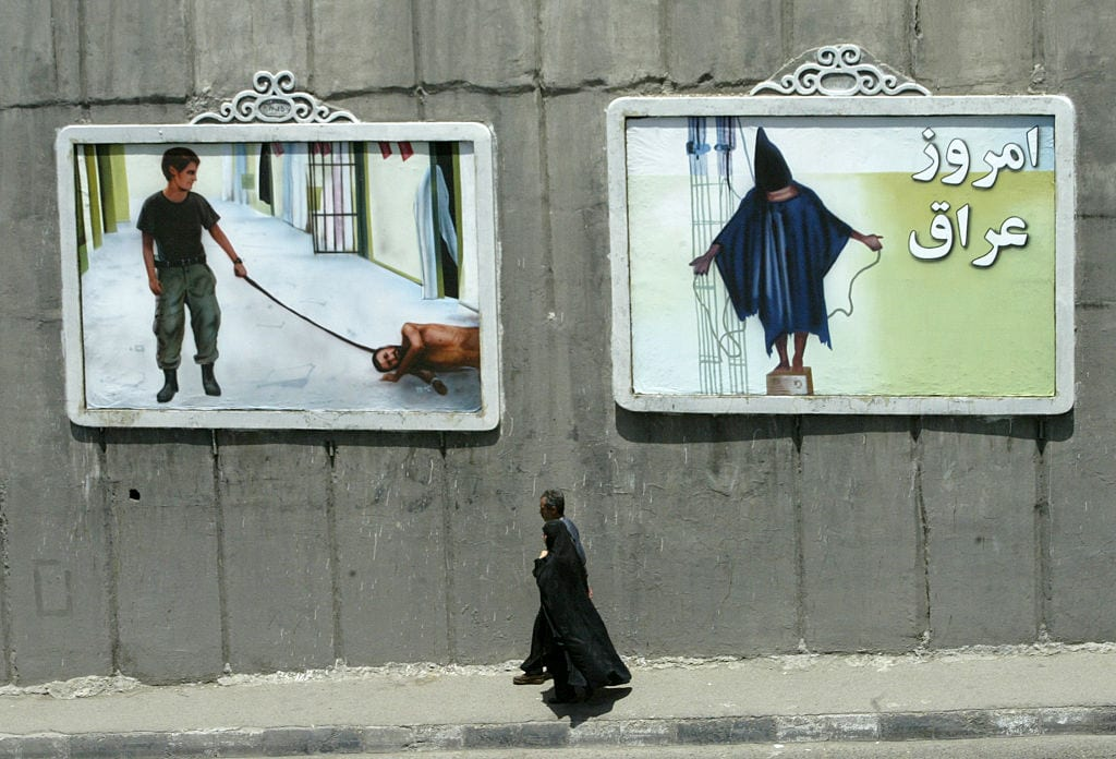 An Iranian couple walk past mural paintings depicting scenes from the torture of Iraqi prisoners by US soldiers at the Abu Ghraib prison near Baghdad, on a major highway in the Iranian capital 1 Tehran June 2004. [BEHROUZ MEHRI/AFP/Getty Images]