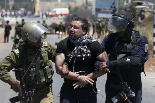 Israeli security forces detain a Palestinian demonstrator during clashes following a Friday noon prayer in solidarity with Palestinian prisoners held in Israeli jails, on May 26, 2017 in Beita, southeast of Nablus, in the Israeli-occupied West Bank. [AFP PHOTO / JAAFAR ASHTIYEH / Getty]