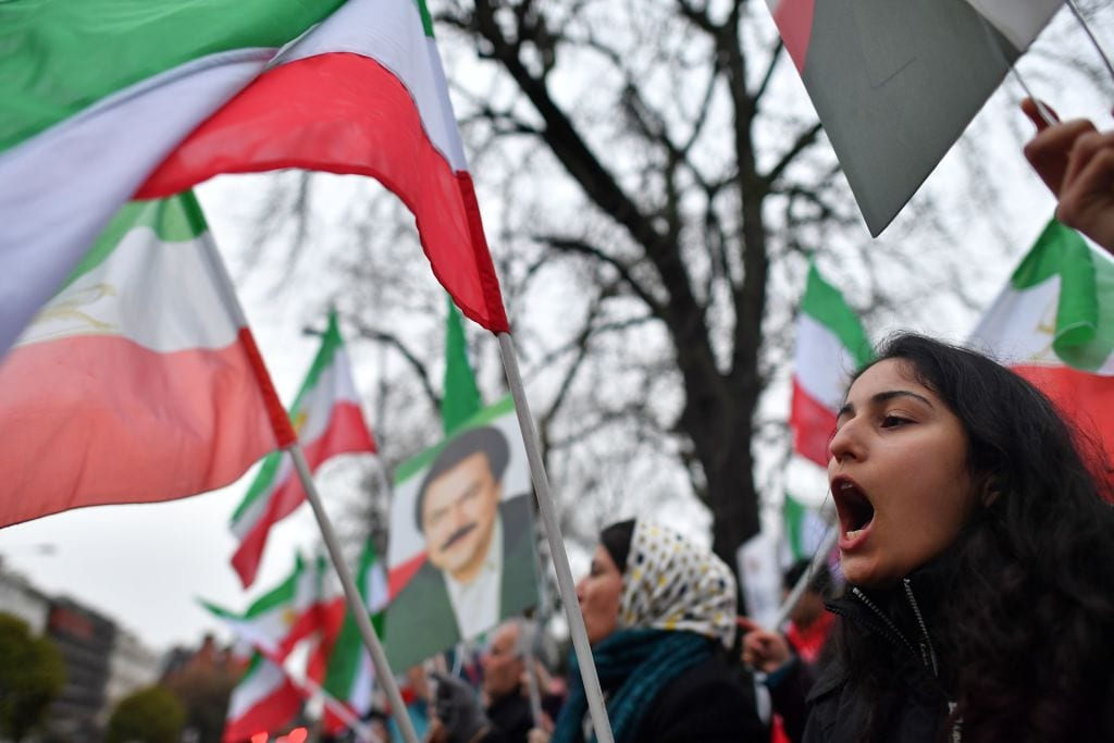 Protesters wave flags as they gather outside the Iranian Embassy in central London on 2 January, 2018 [BEN STANSALL/AFP/Getty Images]