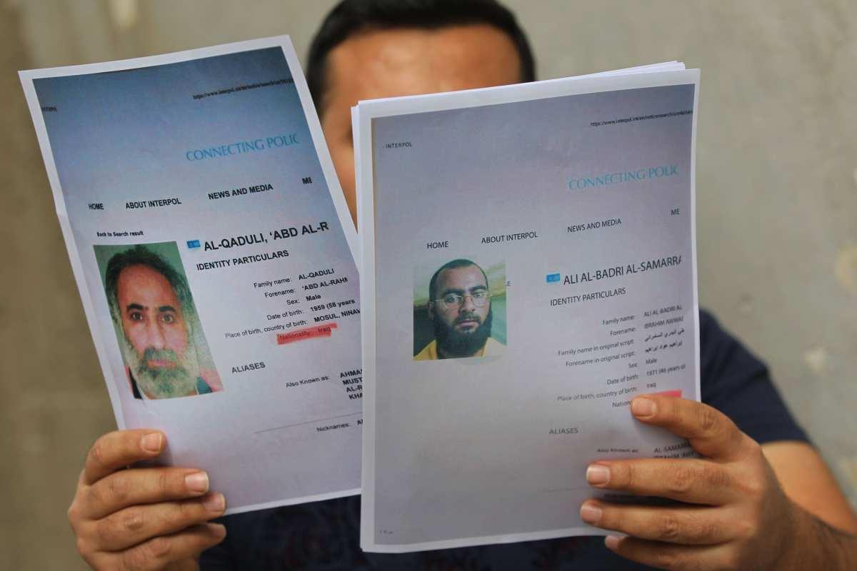 An Iraqi man holds printed profiles of Abu Bakr Al-Baghdadi (R) and his deputy Abd Al-Rahman Al-Qaduli released by Iraqi authorities on 6 February 2018 [AFP PHOTO / AHMAD AL-RUBAYE / Getty]