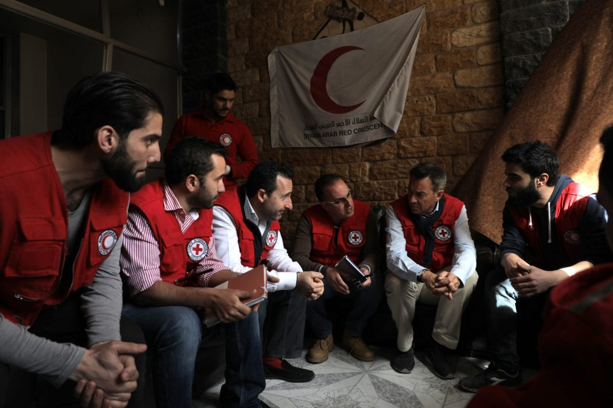 Peter Maurer (2R) President of the International Committee of the Red Cross (ICRC) talks with aid workers after arriving in the rebel-held town of Douma in Eastern Ghouta with a convoy carrying food aid on March 15, 2018. [AFP PHOTO / HAMZA AL-AJWEH / Getty]