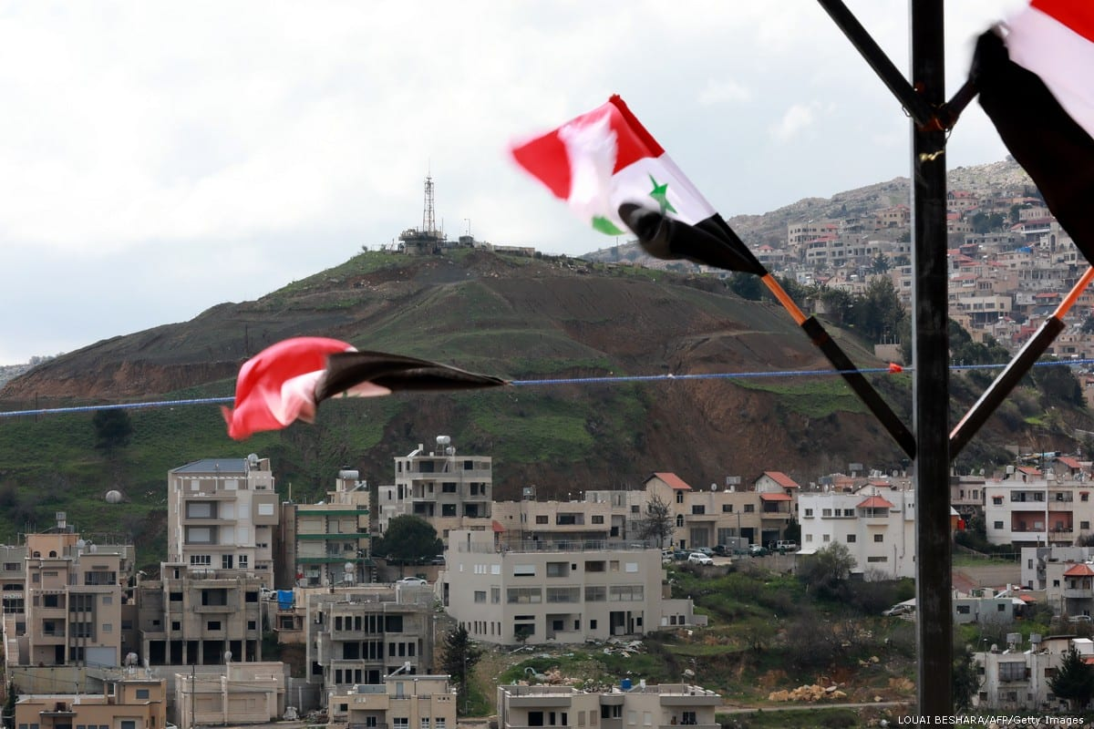 Syrian national flags are flown in the Syrian town Ain Al-Tineh across the Israeli- annexed Golan Heights on 26 March 2019 [LOUAI BESHARA/AFP/Getty Images]