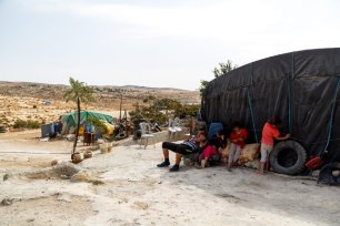 16-year-old Oudi sits outside his home with four girls from the neighbours family