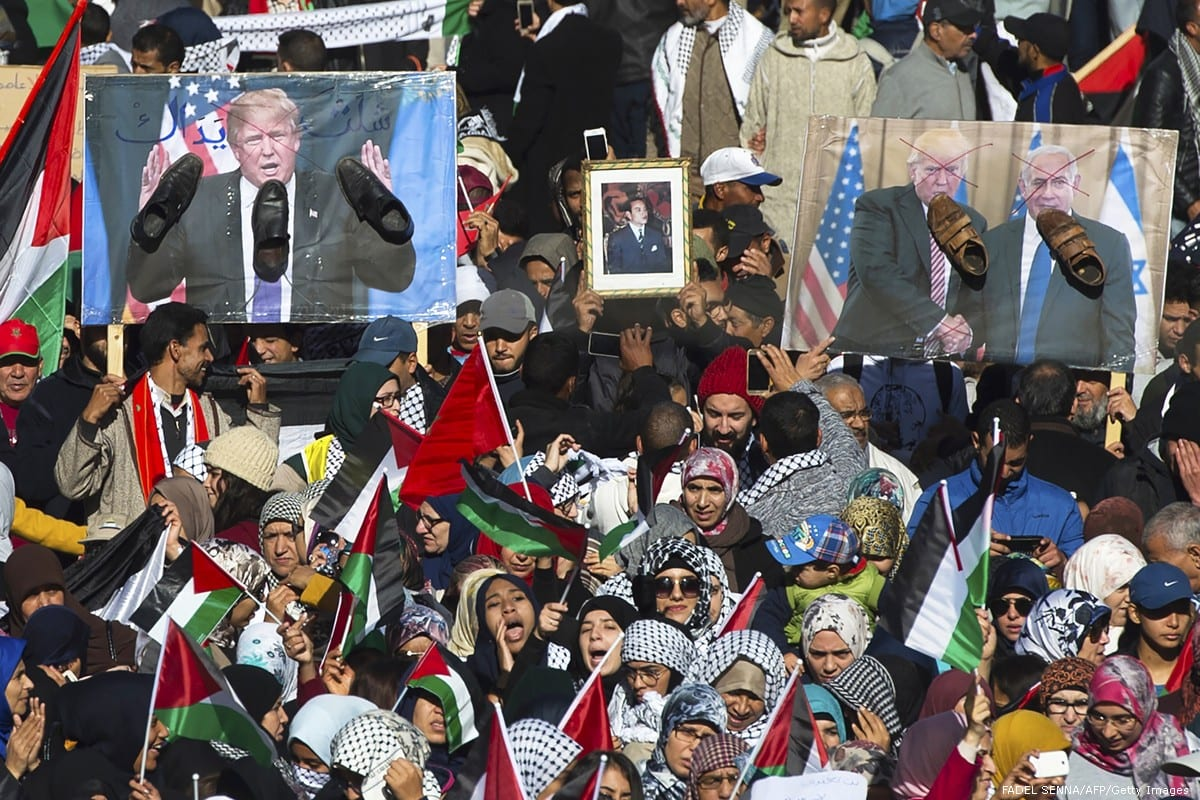 Pro-Palestinian protesters wave Palestinian and Moroccan flags next to posters of the US President Donald Trump and Israeli Prime Minister covered in shoes in a sign of disrespect during a demonstration in Rabat, Morocco on 10 December 2017 [FADEL SENNA/AFP/Getty Images]