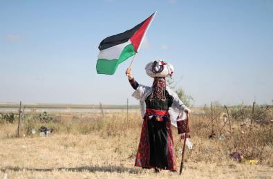 """Meryem Ebu Mousa, 58, who has 6 children, poses for a photo with a walking stick and waves a Palestinian flag during a protest within the """"Great March of Return"""" demonstration in Gaza City, Gaza on 11 May, 2019 [Mustafa Hassona/Anadolu Agency]"""