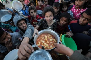 Palestinian kids are seen as they get their iftar meal, distributed by benefactors, in Rafah, Gaza on 9 May, 2019 [Mustafa Hassona/Anadolu Agency]