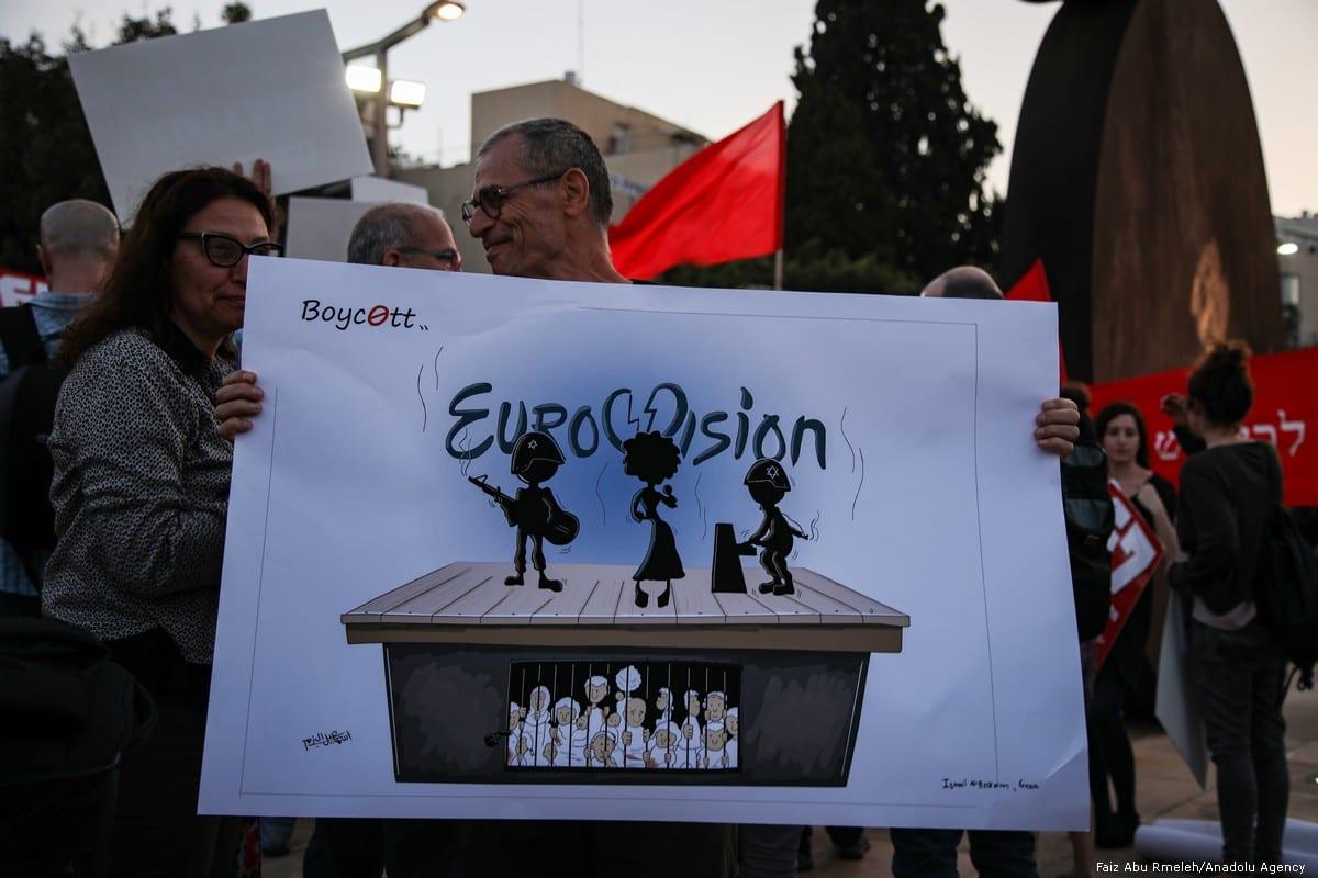 Pessoas seguram cartazes durante um protesto contra o Festival Eurovisão da Canção exigindo a remoção da continuação do bloqueio de Israel a Gaza na Praça Habima em Tel Aviv em 14 de maio de 2019 [Faiz Abu Rmeleh / Agência Anadolu]