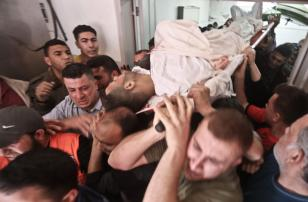 Palestinians carrying a victim of Israeli strikes on 5 May, 2019 [Mohammed Asad/Middle East Monitor]