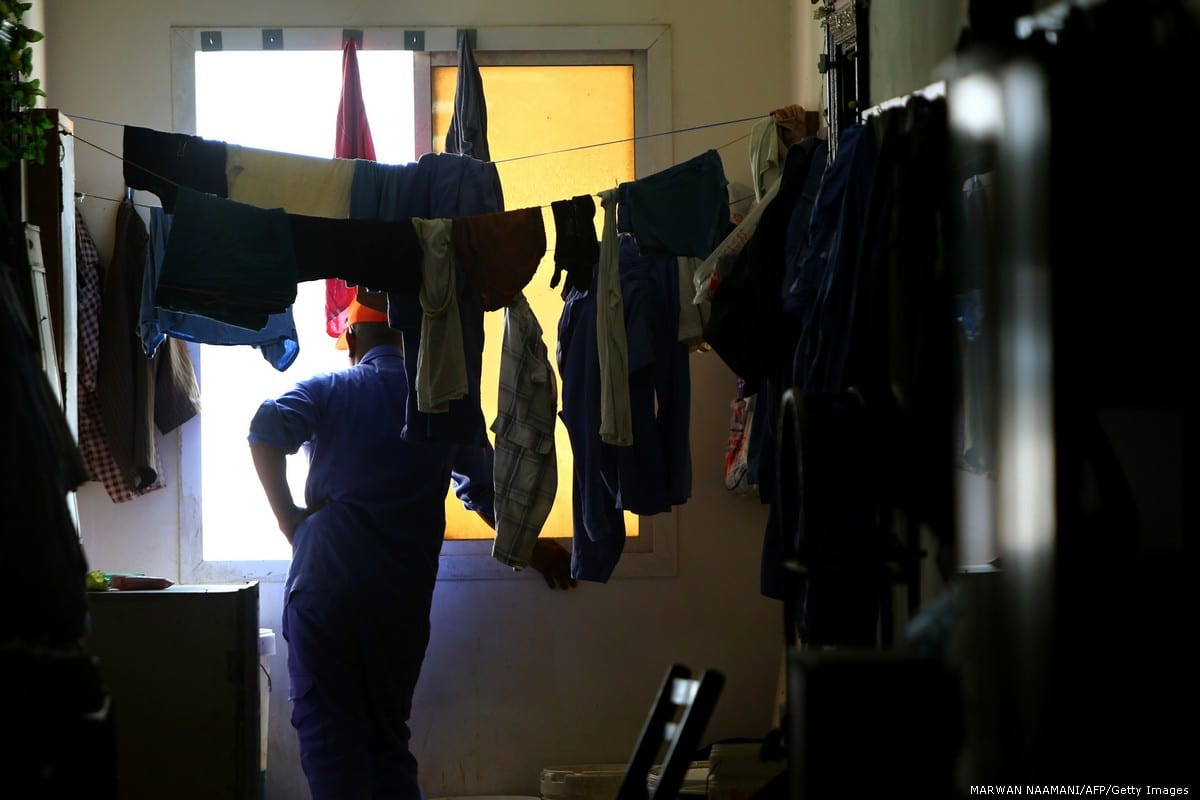 A worker from Nepal looks out from the window of his room at a private camp housing foreign workers in Doha,Qatar on 3 May 2015 [MARWAN NAAMANI/AFP/Getty Images]