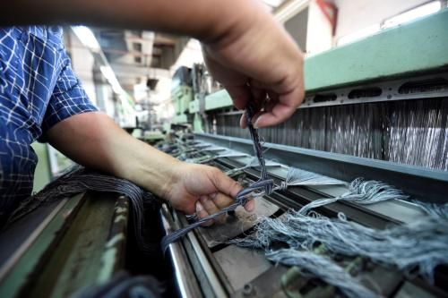An Egyptian worker preparing threads on a machine at the Marie Louis textile clothing and textile factory in the 10th of Ramadan city, about 60 kms north of Cairo, on 29 July 2018 [Khaled DESOUKI / AFP / Getty]