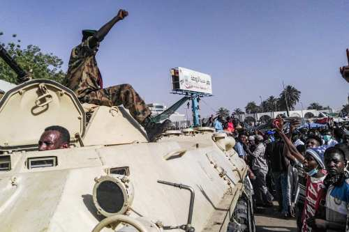 Sudanese protesters salute a military armoured vehicle as they gather during a demonstration in front of the military headquarters in the capital Khartoum on 9 April 2019 [AFP/Getty]