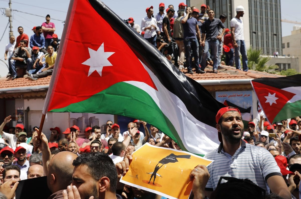 Jordanian protesters wave national flags and shout slogans during an anti-austerity rally, on 6 June 2018 in front of the Labor Union offices in Amman. [AHMAD GHARABLI / AFP/ Getty]