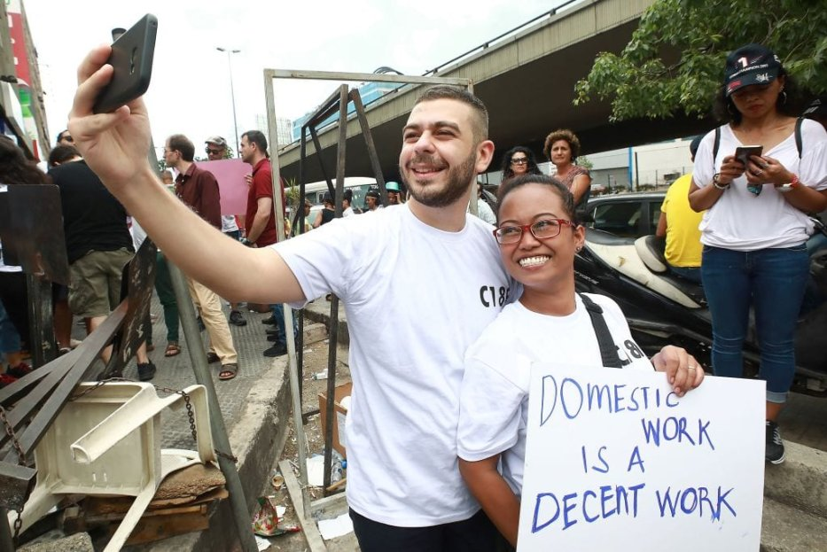 A Migrant domestic worker takes a selfie with a protester as they demonstrate in the northern suburbs of Beirut to protest against abuses and ask for law protection, on June 24, 2018. [ANWAR AMRO/AFP/Getty Images]