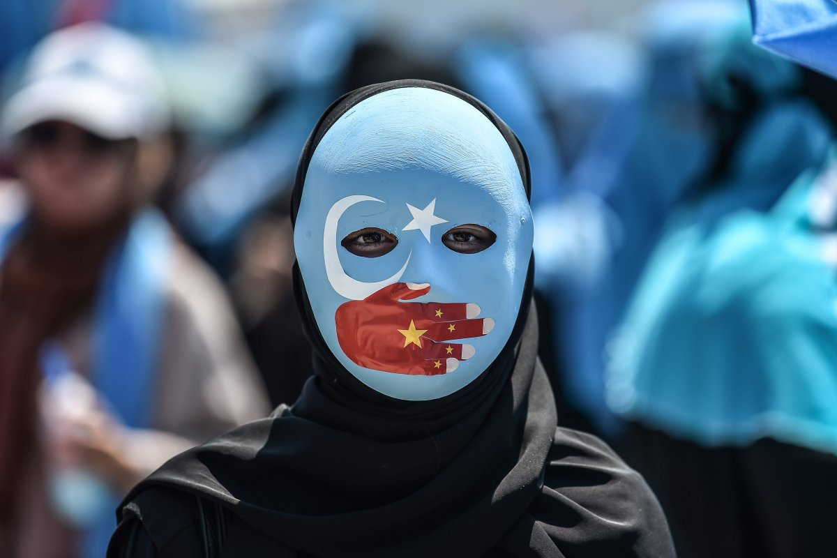 A demonstrator wearing a mask painted with the colours of the flag of East Turkestan and a hand bearing the colours of the Chinese flag attends a protest in of the mostly Muslim Uighur minority on 5 July 2018 [OZAN KOSE/AFP/Getty]