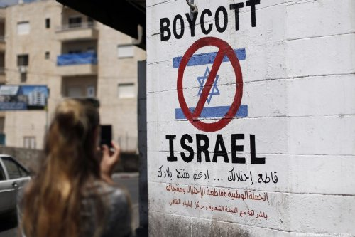A tourist photographs a sign painted on a wall in the West Bank biblical town of Bethlehem on June 5, 2015, calling to boycott Israeli products coming from Jewish settlements [THOMAS COEX/AFP/Getty Images]