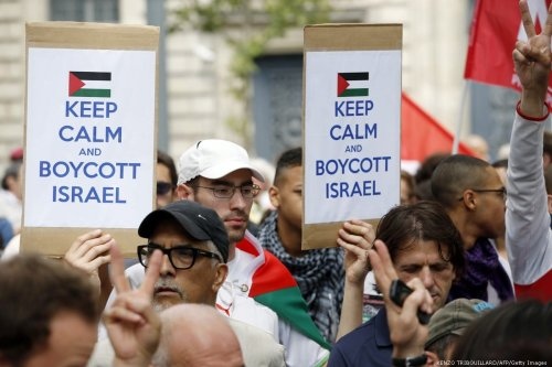 A Pro-Palestinian demonstrators carry placards reading 'Keep calm and boycott Israel' on 26 July 2014 [KENZO TRIBOUILLARD/AFP/Getty Images]