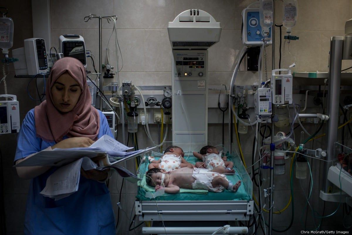 A nurse looks over documents next to newborn babies, 19 July 2017 [Chris McGrath/Getty Images]