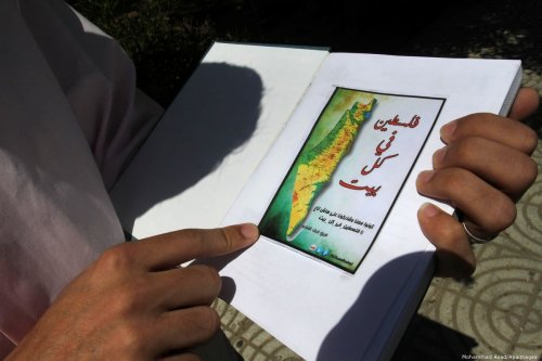 Palestinian man with a map of Palestine in Gaza city, 20 June 2013 [Mohammed Asad/Apaimages]